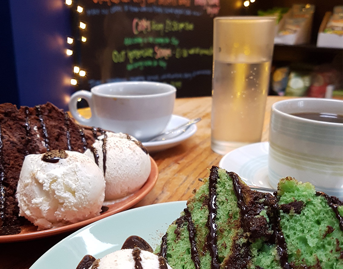 chocolate cake and mint cake both with ice cream, cups of coffee and water in a cafe