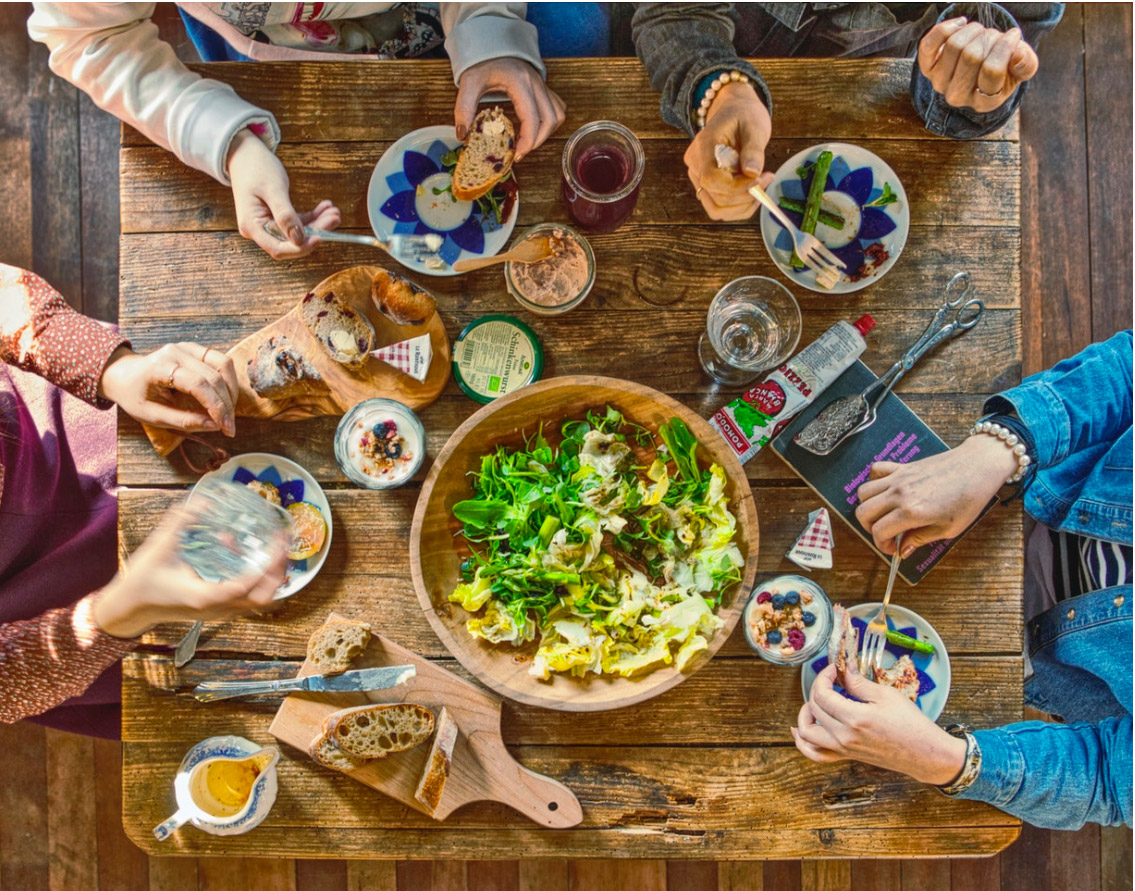 Overhead tabletop shot of four people enjoying a meal with large salad bowl