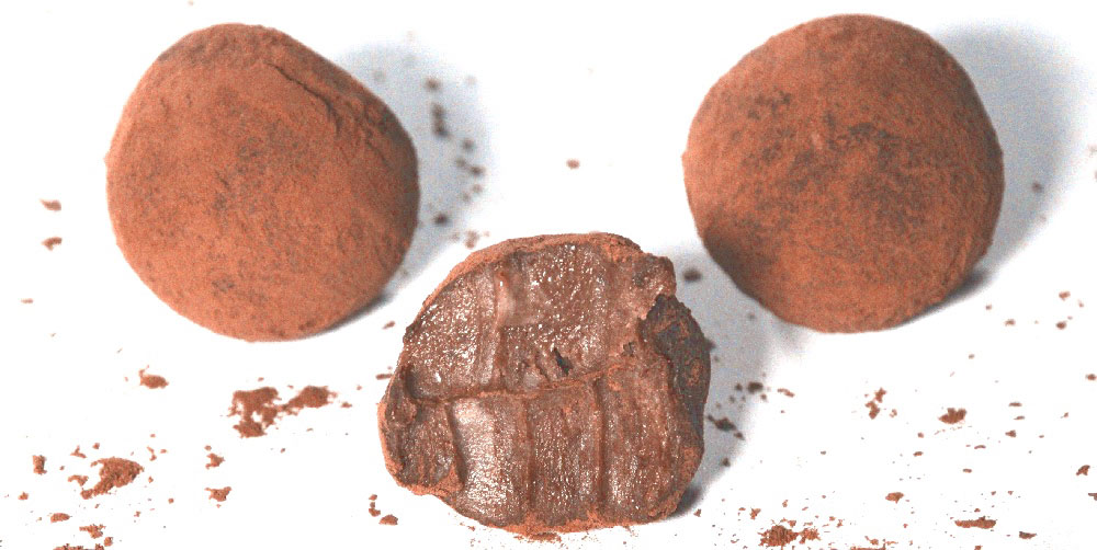 Thre truffles, with the middle one having a bite taken out of it.