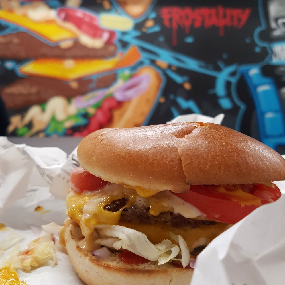 Close up of vegan burger in a bun with salad against a graffiti style wall