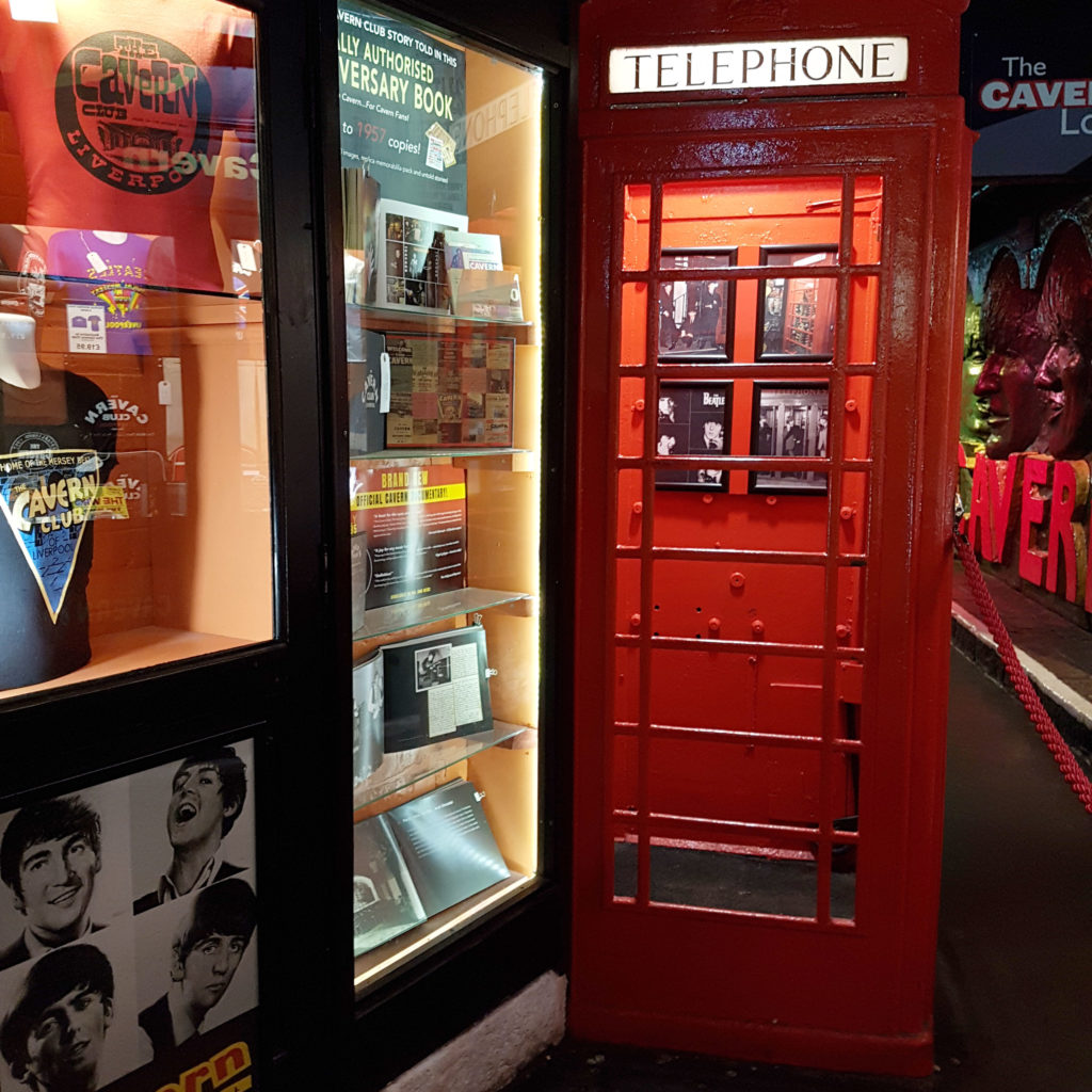 Red Britiesh Telephone box in the Cavern Club next to a display of Beatles memorabillia